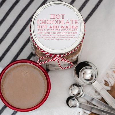 Keto hot chocolate mix recipe in a mason jar with a mug of keto hot chocolate and instructions for how to make keto hot chocolate.