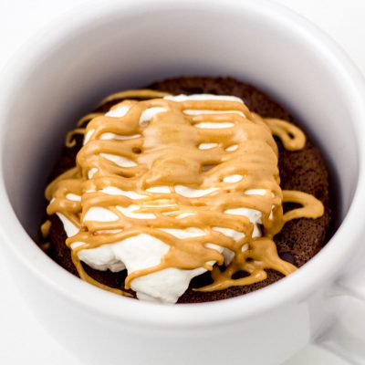 Low carb and keto chocolate mug cake in a mug, topped with whipped cream and sugar free peanut butter.
