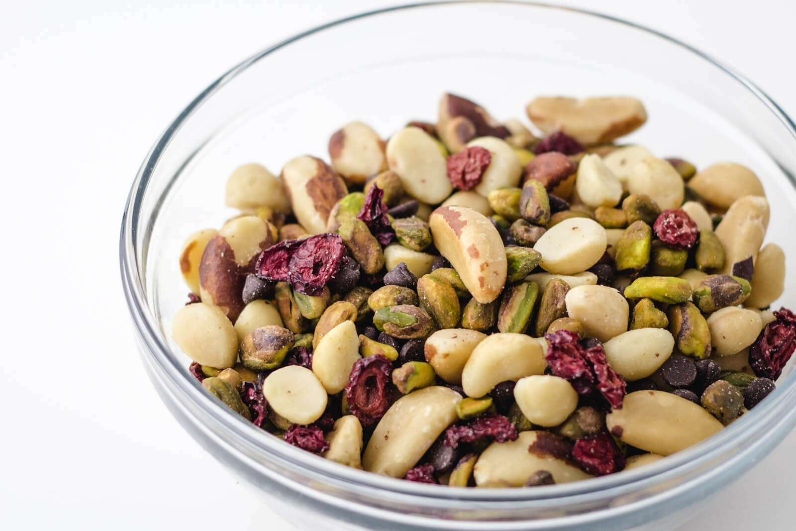 Bowl of low carb keto trail mix with brazil nuts, macadamias, pistachios, lily's chocolate chips, and honestly cranberry unsweetened dried cranberries
