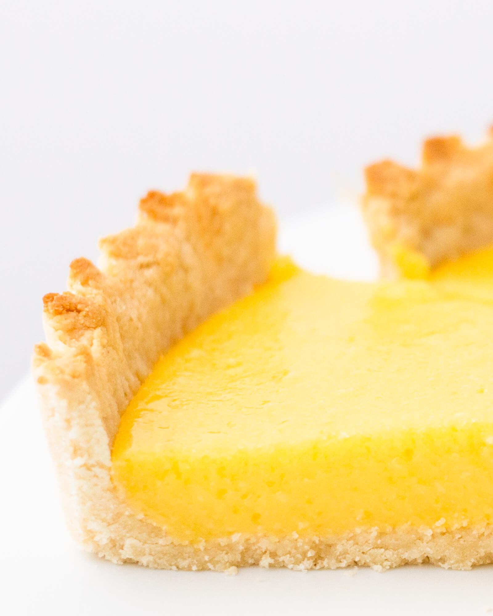 Slice of low carb tart, made from my sugar free lemon curd tart recipe with diabetic friendly shortbread crust on a white cake stand.