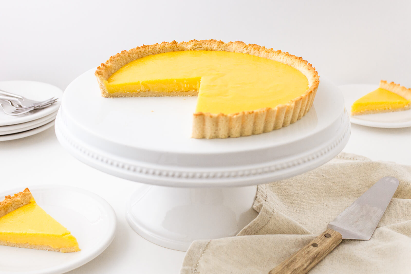 (-inch keto lemon curd tart on a white cake stand with two plates of low carb lemon curd tart slices, stack of white plates, and serving utensils for the tart