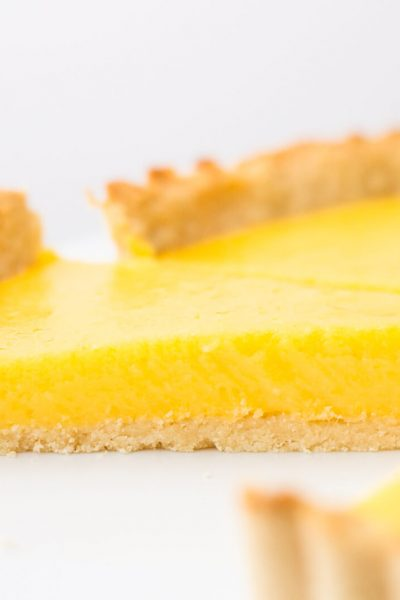 Slice of keto lemon curd tart with low carb shortbread crust on a white cake stand