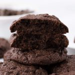 Stack of low carb chocolate chocolate chip cookies with one double chocolate chip cookie broken in half