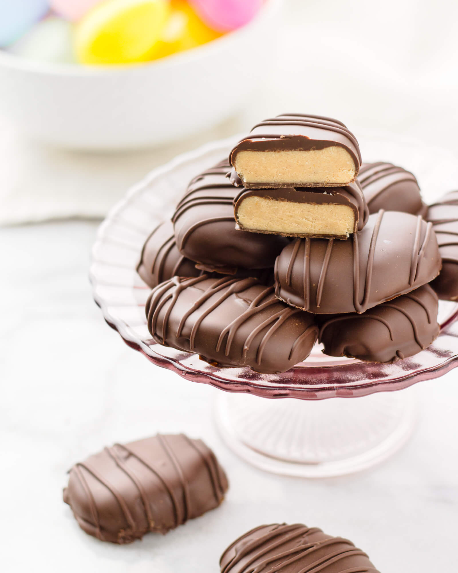 eat healthier homemade reeses peanut butter eggs for and Easter treat this year, chocolate dipped eggs displayed on a pink cake stand with colorful Easter eggs in the background, vegan option and coconut flour free with nut free option