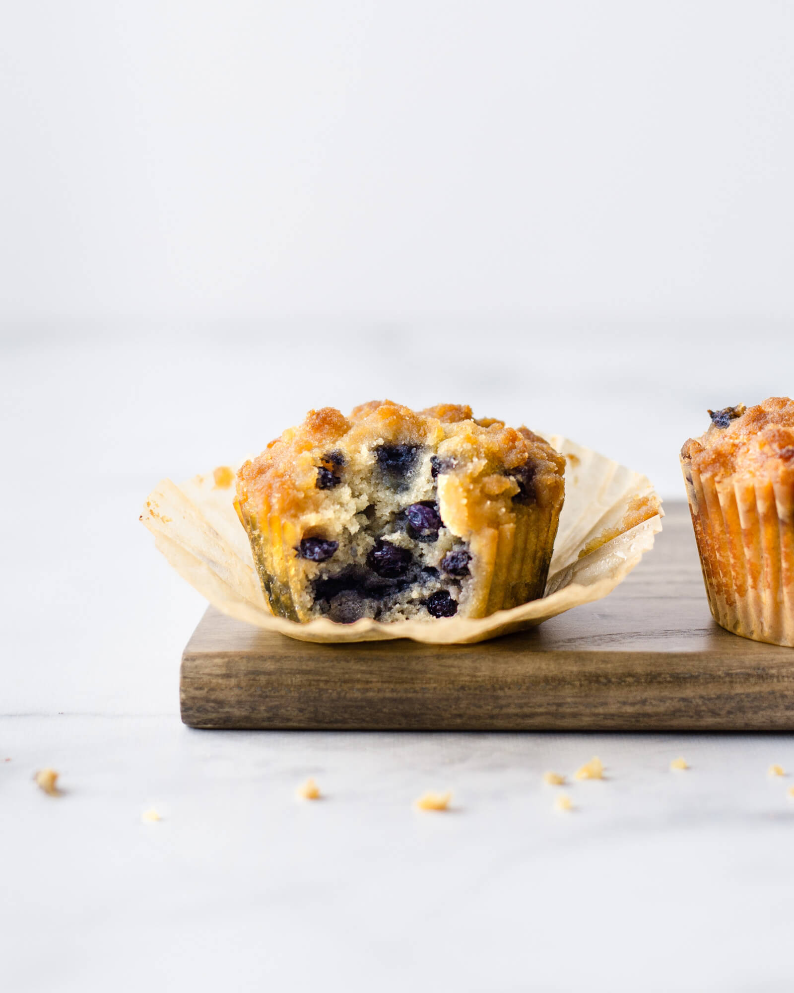 The best low carb blueberry muffin recipe made with coconut flour shown on wood cutting board and nonstick parchment muffin liner with bite taken and crumble topping