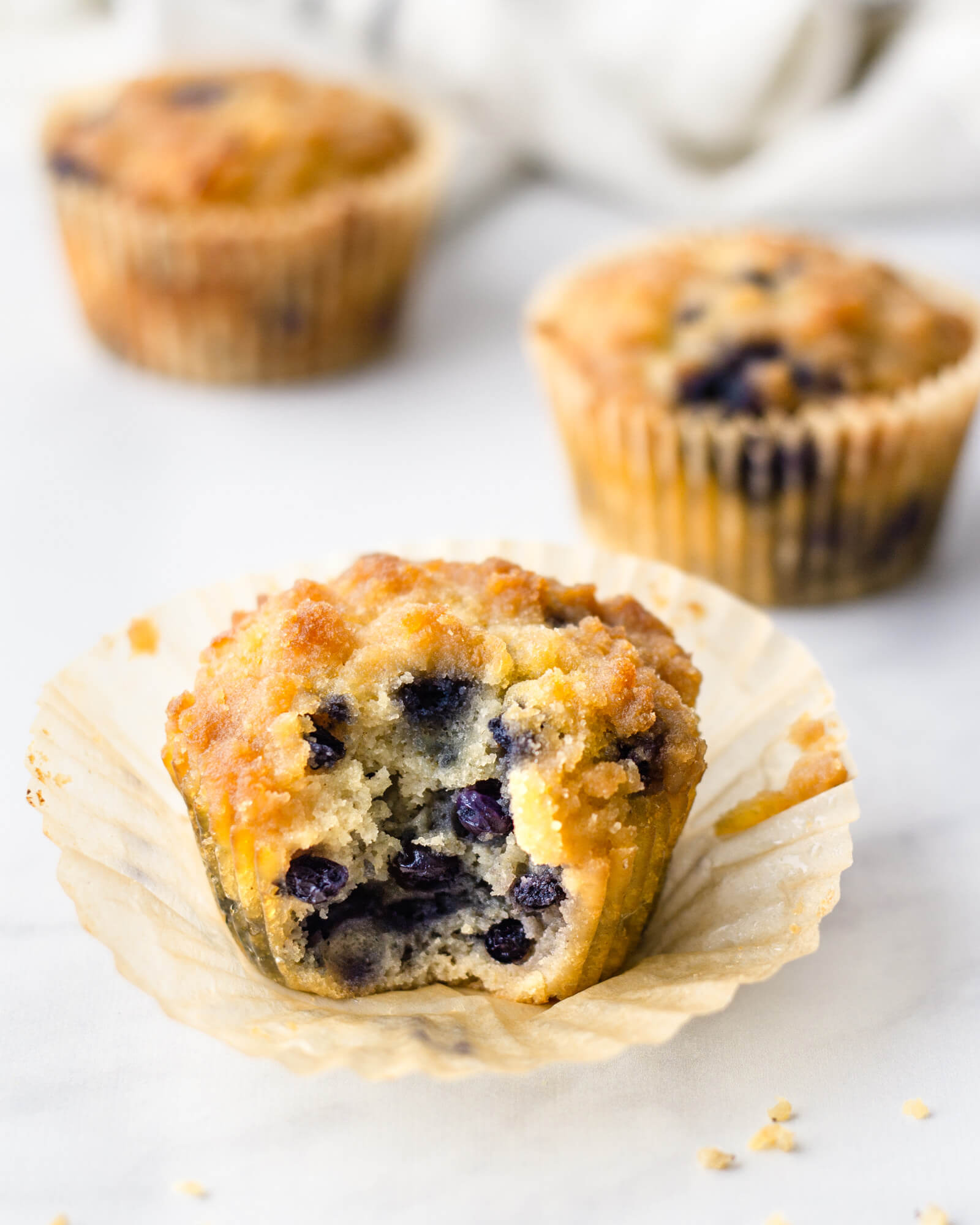 Keto blueberry muffin made with coconut flour and crumb topping with bite taken on nonstick cupcake liner