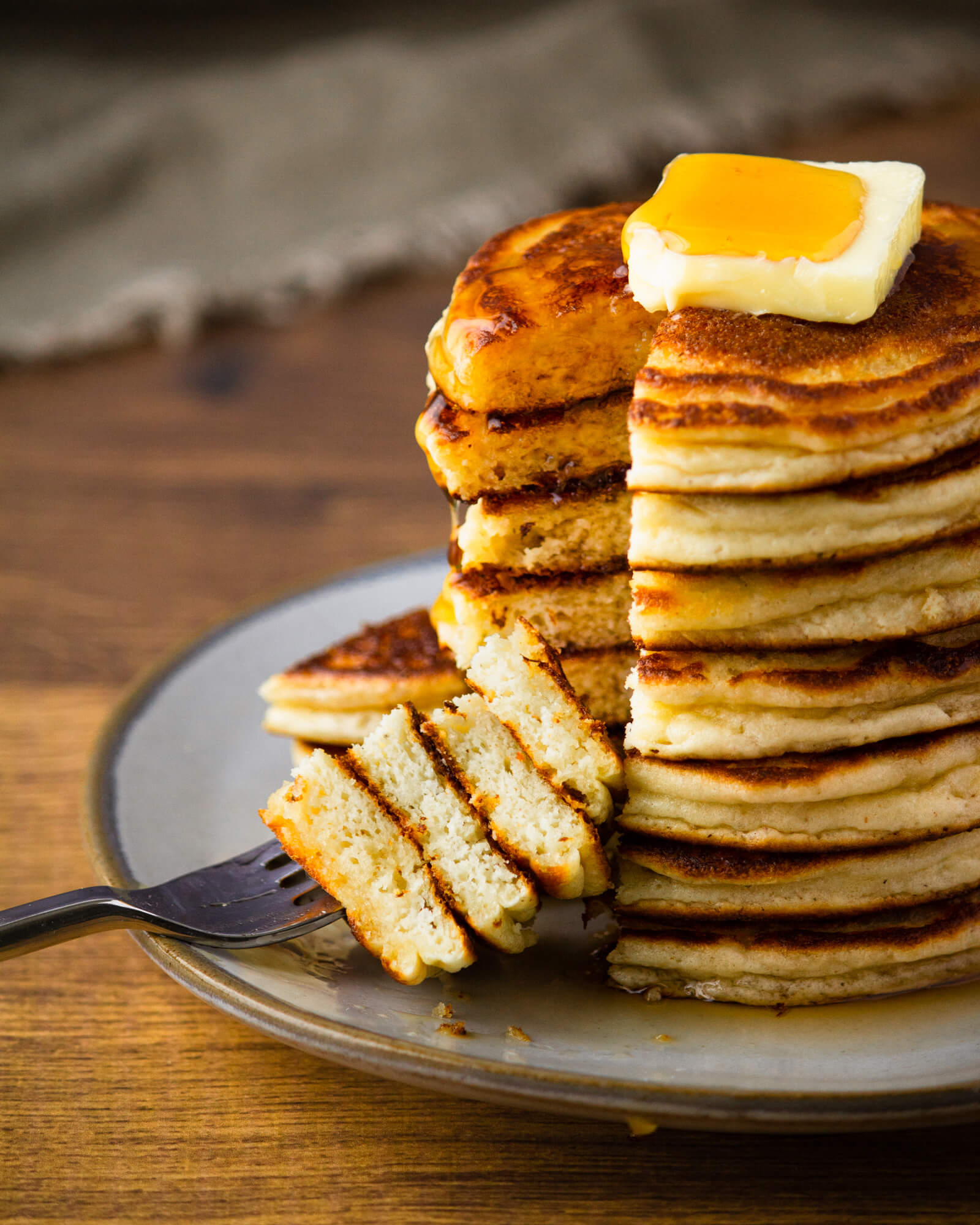 Stack of low carb pancakes made with coconut flour with slice cut out and fork. Topped with sugar free KNOW Better maple flavored syrup and butter.