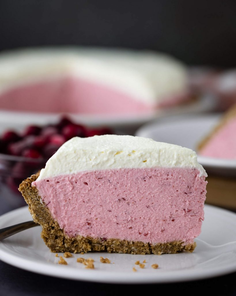 Slice of no bake keto cranberry cheesecake in gingerbread faux graham cracker crust.
