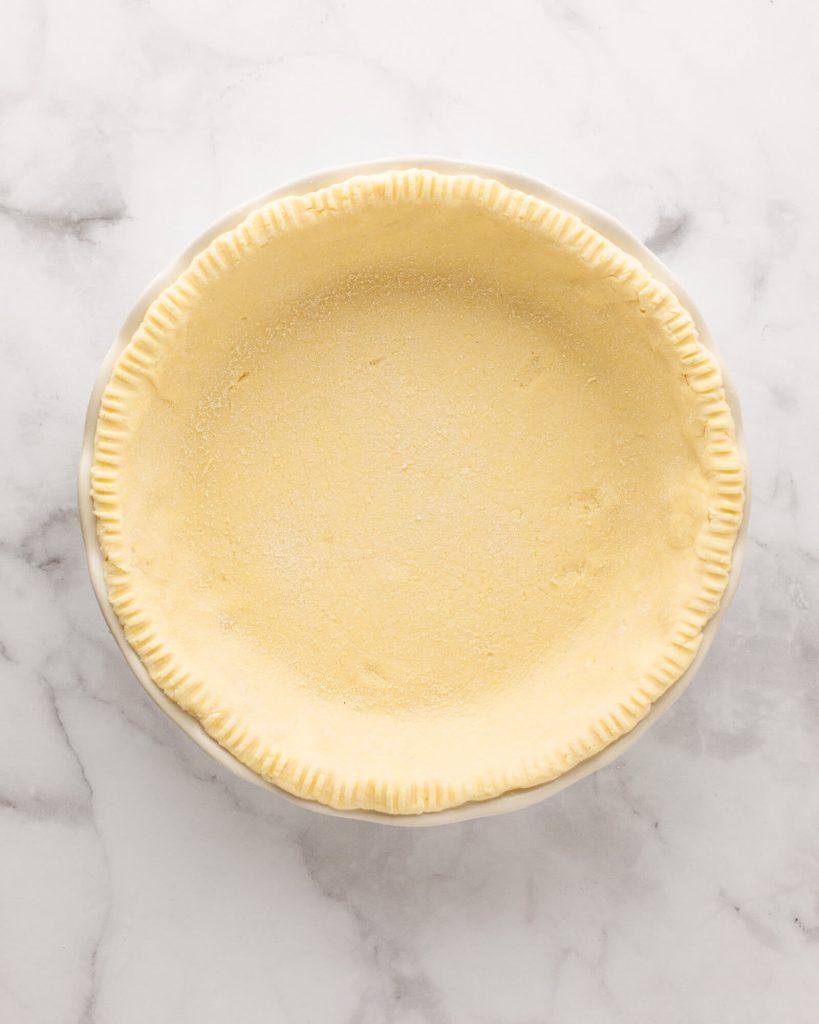 Coconut flour pie crust dough in a pie pan ready to bake.