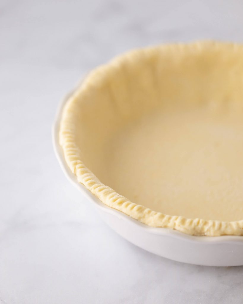 Easy tender and flaky all butter keto pie crust dough in the pie pan ready to bake
