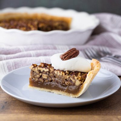 Slice of keto pecan pie served with sugar free whipped cream