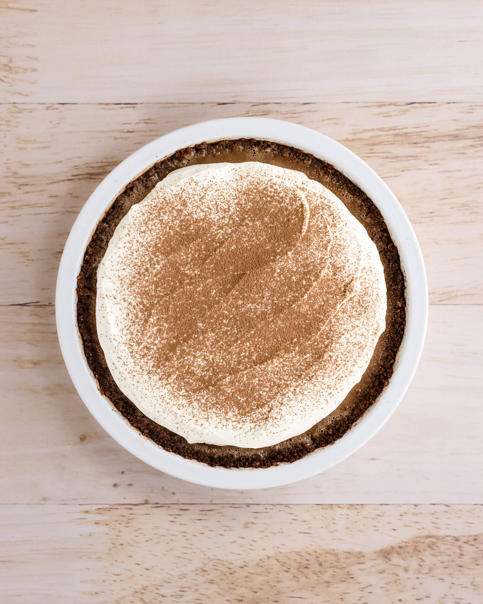 Full sugar free chocolate pie with keto whipped cream topping shot from overhead. Dusted with cocoa powder.