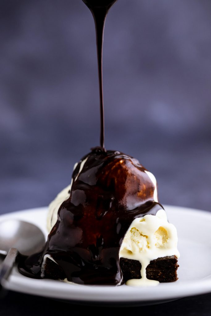 Sugar free chocolate sauce being drizzled onto a keto ice cream brownie sundae